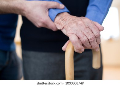 Senior Man's Hands On Walking Stick With Care Worker In Background