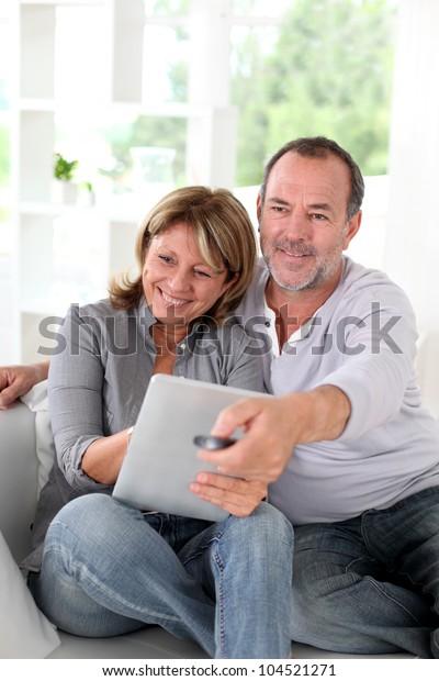 Senior married couple choosing movie on tv
