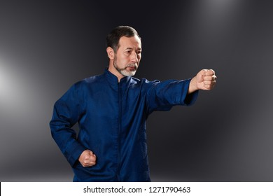Senior master practicing qi qong taijiquan at studio. Breathing exercise and martial art moves, traditional chinese qi energy management gymnastics
