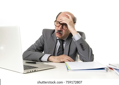 senior mature business man with bald head on his 60s working stressed and frustrated at office computer laptop desk looking tired and overwhelmed in job problems and overwork suffering headache