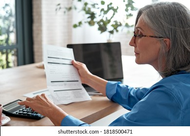 Senior mature business woman holding paper bill using calculator, old lady managing account finances, calculating money budget tax, planning banking loan debt pension payment sit at home office table. - Shutterstock ID 1818500471