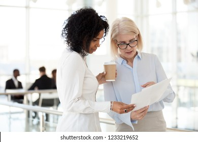 Senior mature caucasian female executive ceo discuss report with young mixed race black colleague, serious old aged mentor reads paper explains business plan to african employee intern talk in office