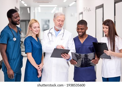 Senior mature doctor in white uniform consulting young doctors therapists using clipboard