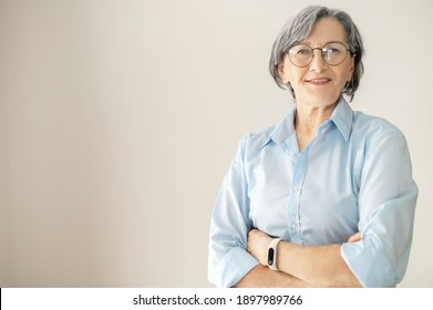 Senior mature gray-haired female professional office worker portrait, elder businesswoman in glasses standing in the office and confidently looking at the camera, having arms folded
