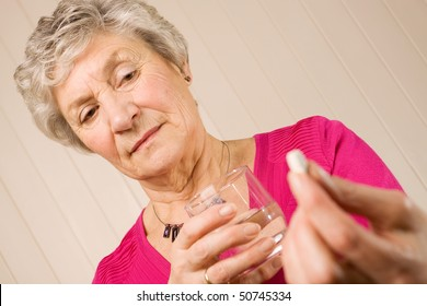 Senior mature lady holding a tablet or pill in one hand and a glass of water in the other