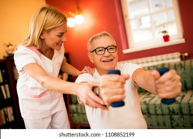 Senior mature man doing exercises with dumbbells while nurse helps to them