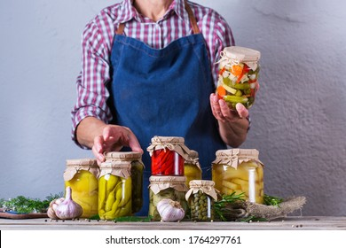 Senior mature woman holding in hands jar with homemade preserved and fermented food. Variety of pickled and marinated vegetables. Housekeeping, home economics, harvest preservation