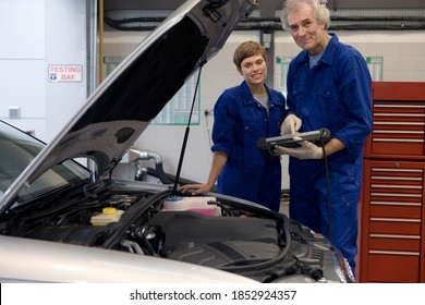 Senior mechanic and his colleague standing next to the open hood of a broken down car and posing with a diagnostic computer