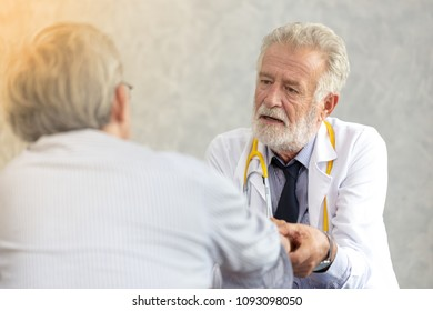 Senior medical doctor or chief doctor giving a consultation to her male patient and explaining medical informations and diagnosis at the clinic or hospital.