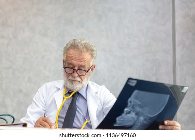 Senior medical doctor or chief doctor or Surgeon are checking skull of human head via x-ray film In examination room with copy space.