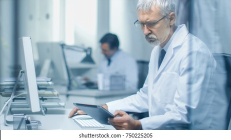 Senior Medical Practitioner Sitting Before Personal Computer Uses Tablet Computer with His One Hand and Operates Keyboard with Other. His Assistant Working in Background.