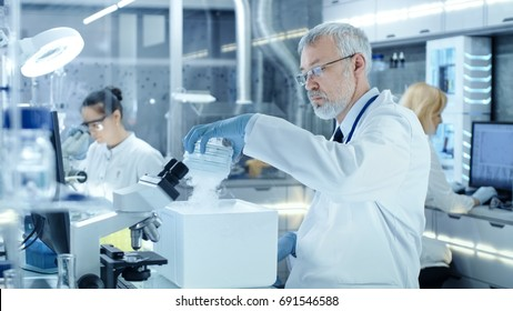 Senior Medical Research Scientist Takes Out Petri Dish with Samples from Opened Refrigerator Box. He Works in a Busy Modern Laboratory Center.