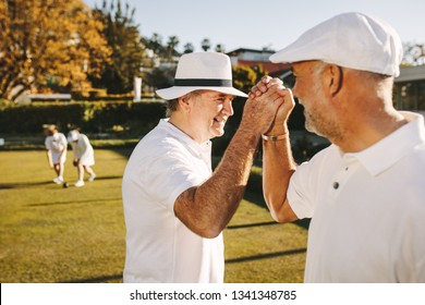 Senior men giving high five celebrating success. Elderly people enjoying a game of boules in a park.