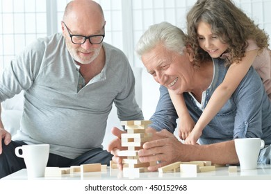 senior men and granddaughter with  board game