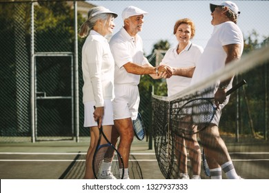 Senior men shaking hands standing near the net after the game. Happy seniors greeting each other after a game of mixed doubles tennis.