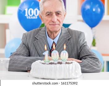 Senior men sitting front of cake for 100th birthday