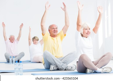 Senior men and women during fitness classes, stretching their arms while sitting with crossed legs on exercise mats