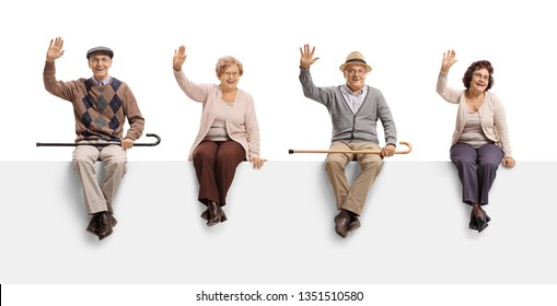 Senior men and women sitting on a blank billboard sign and waving at the camera isolated on white background