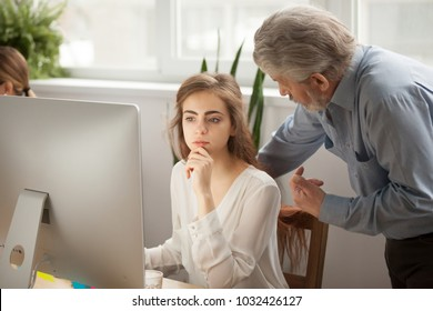 Senior mentor teaching female intern using computer in office, old executive training young focused manager listening explanation of aged corporate teacher boss helping giving instructions concept