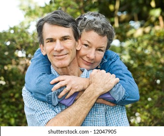 Senior or middle age couple outdoors hugging, sharing an affectionate moment.
