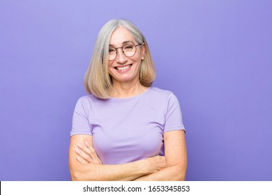 senior or middle age pretty woman looking like a happy, proud and satisfied achiever smiling with arms crossed