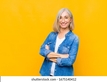 senior or middle age pretty woman laughing happily with arms crossed, with a relaxed, positive and satisfied pose