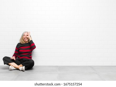 senior or middle age pretty woman smiling happily with funny face, joking and looking through peephole, spying on secrets