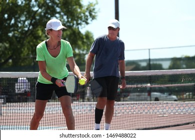 A senior mixed doubles team competes in a pickleball tournament