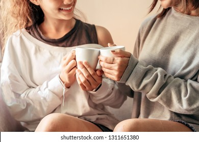 Senior mom and her daughter are hugging, smiling and dringking a warm coffee in some morning.