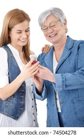 Senior mother and attractive young daughter looking at photos on mobile phone, smiling happily.?