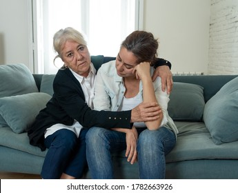 Senior mother comforting adult daughter grieving loss of loved one fighting the Coronavirus. Elderly mother embracing adult daughter suffering from depression. People affected by COVID-19 outbreak.