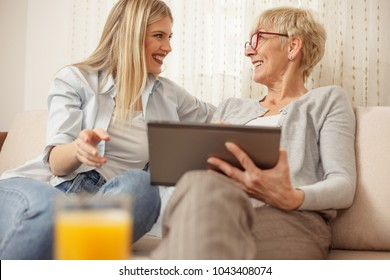 Senior mother and daughter browsing the internet on a tablet. Happy family moments at home.