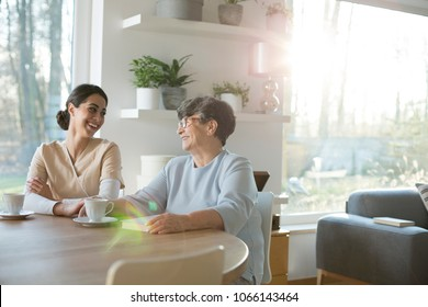 Senior mother and daughter laughing while having a tea and talking