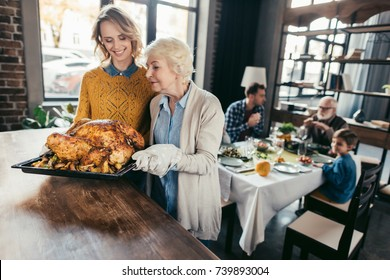 senior mother and daughter with thanksgiving turkey for family dinner at home