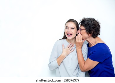 Senior Mother Whispering Secret to Young Daughter