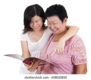 Senior mother and young daughter reading on a book, with smiling, isolated on white background.