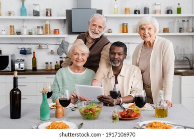 senior multicultural people holding digital tablet near happy friends and tasty food on table