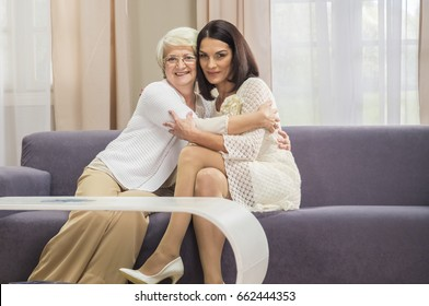 Senior mum proudly holds her daughters hands indoor shot