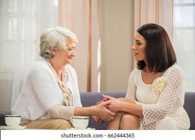Senior mum proudly holds her daughters hands indoor shot