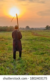 An senior Muslim man in a skullcap and traditional clothes leaves with a hand scythe from the hay field at sunset. Country life concept