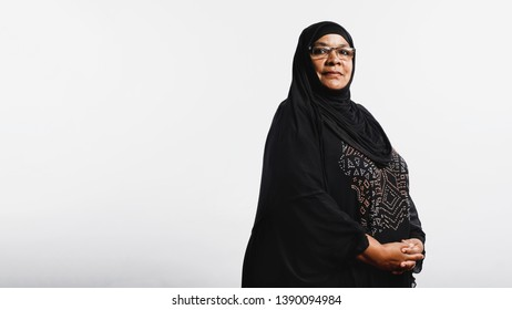 Senior muslim woman in hijab standing against white background. Arabic woman wearing eyeglasses and a black hijab looking at camera.