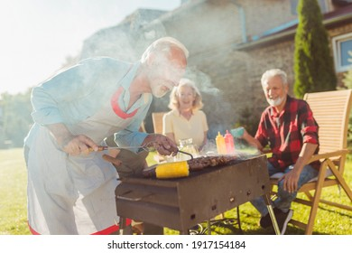 Senior neighbors having fun spending sunny summer day together outdoors, having a backyard barbecue party