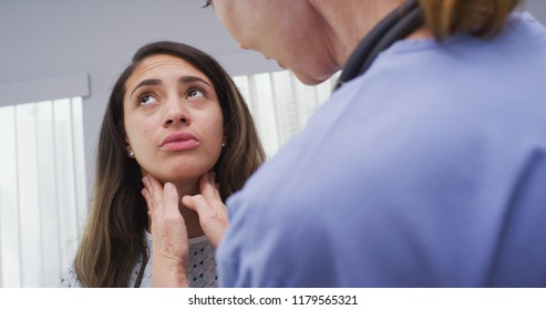 Senior nurse checking young patients neck for swollen lymph nodes