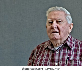 Senior octogenarian old man with pen in pocket of his plaid shirt with gray background.