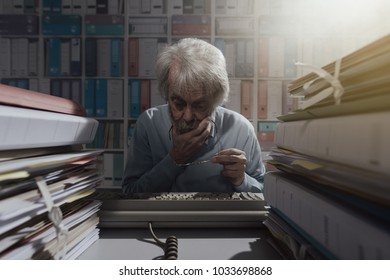 Senior office worker using an obsolete keyboard, he is having difficulties and thinking with hand on chin