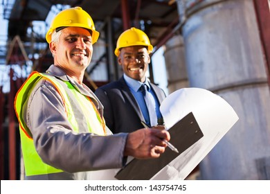 senior oil industry worker holding clipboard and blueprint with manager in plant