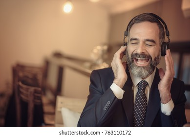 Senior old business man listening to his favourite music through a pair of big headphones in a coffee shop
