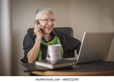 Senior old business woman having a pleasant conversation on her phone in her office