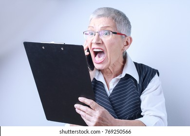 Senior old business woman yelling on her phone, unhappy with a financial report she's reading