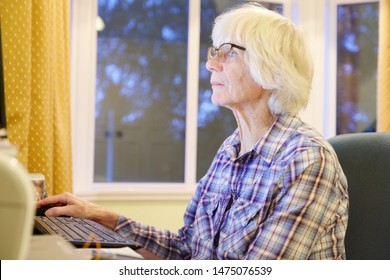 Senior old elderly person learning computer and online pension and banking internet skills protect against fraud uk